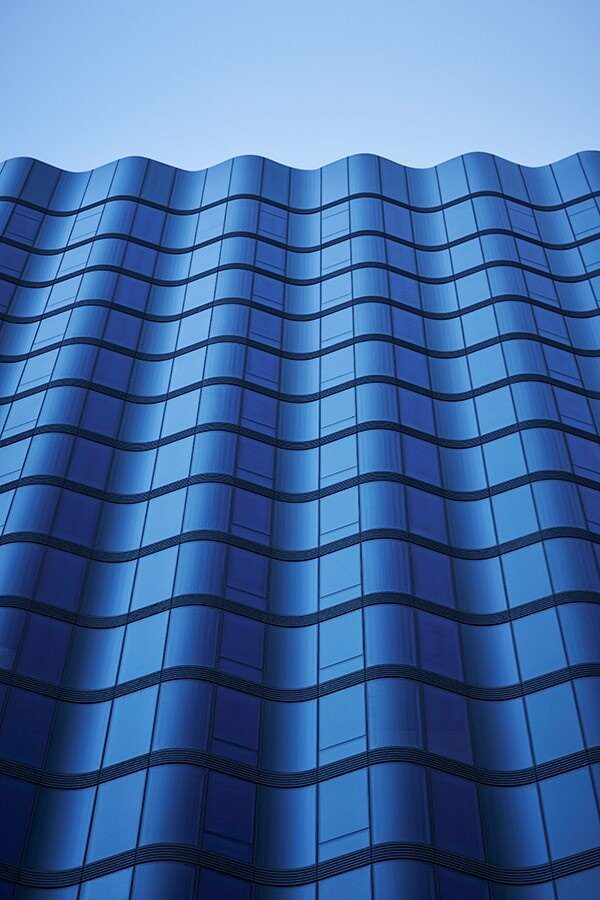A tall builidng with rows of windows along the sides of it with the blue sky on top.