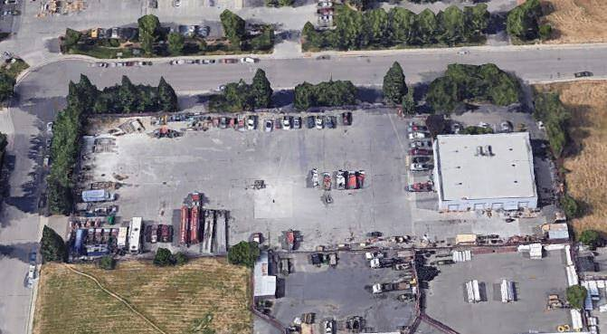 Cars that are parked in a parking lot as viewed from the air near a small building.