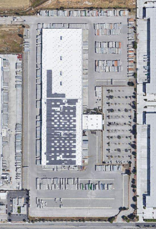 Top view of a white warehouse that is surrounded by a parking lot full of cars and trucks.
