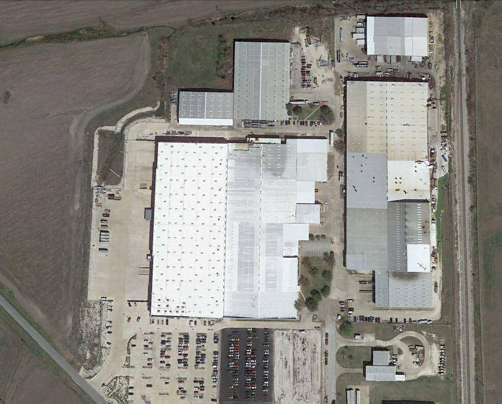 Top view of a group of warehouse with cars and trucks parked in the lot around it.