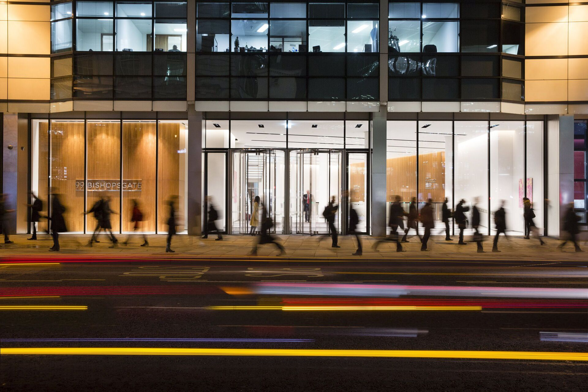 A crowd of people walking along the sidewalk that is in front of a building with glass panels.
