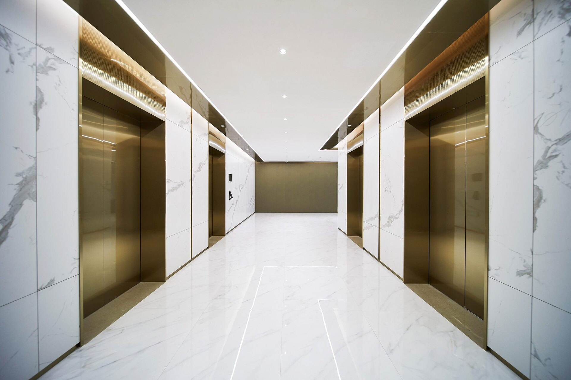 A hallway that has marble walls and gold doors for elevators that can go to different levels.