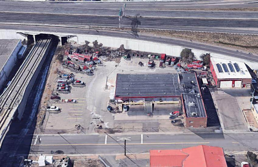 Outdoor view of a lot with several cars and trucks in the lot that is next to a railroad
