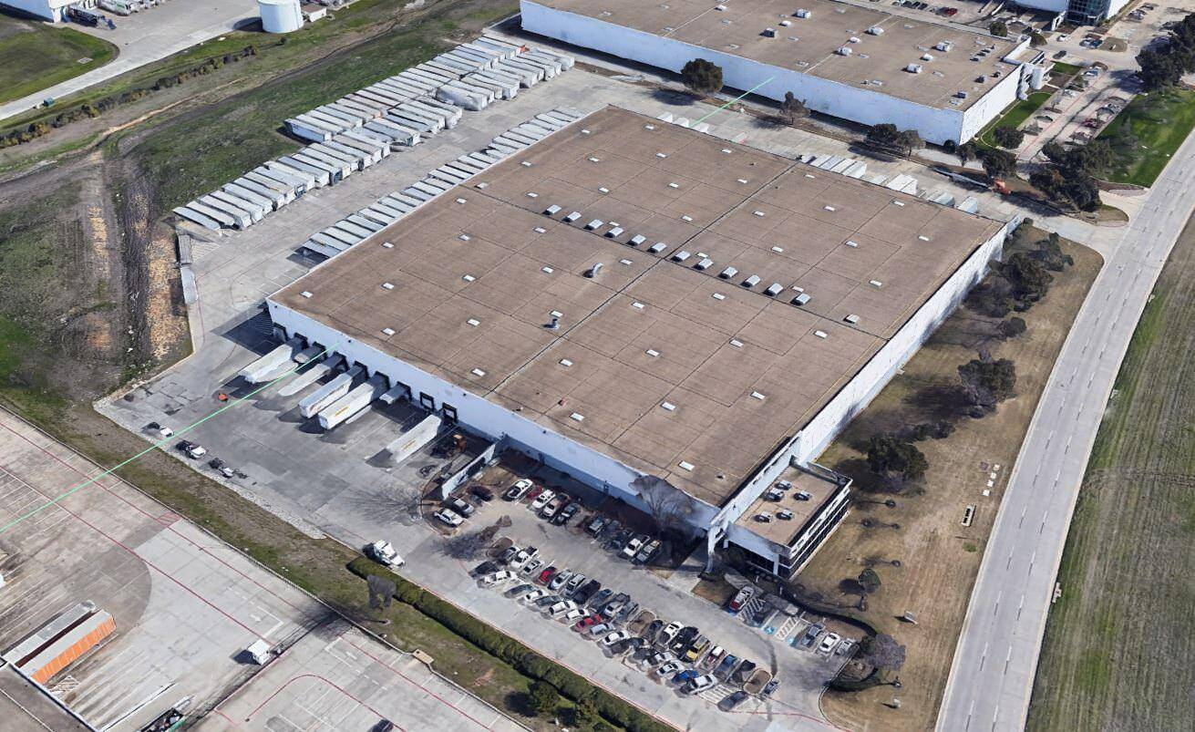 Top view of a large building with a brown roof that has trucks and cars parked in the lot around it.