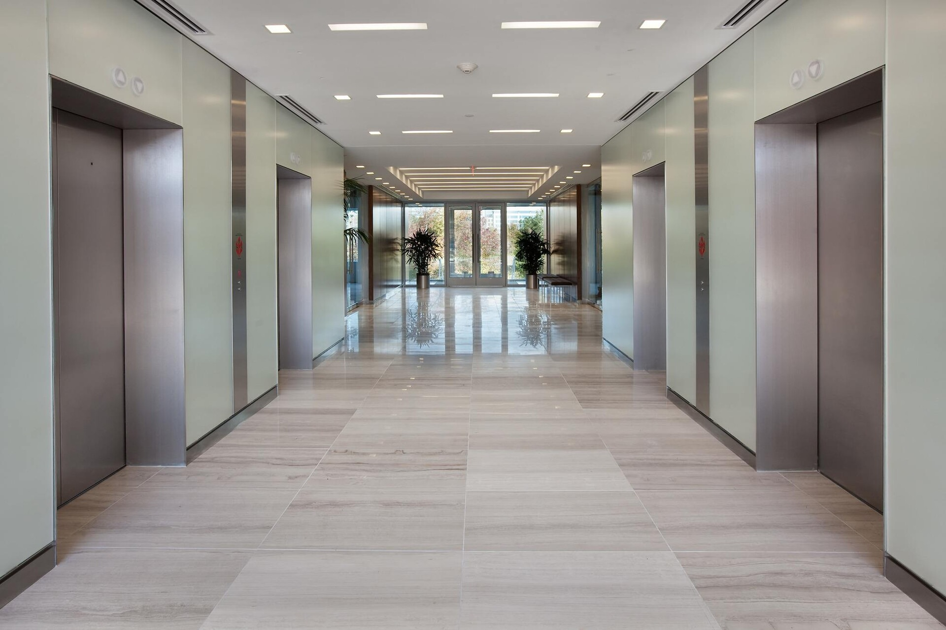 A hallway that is inside of an office building and there are elevators on either side of it to go up.