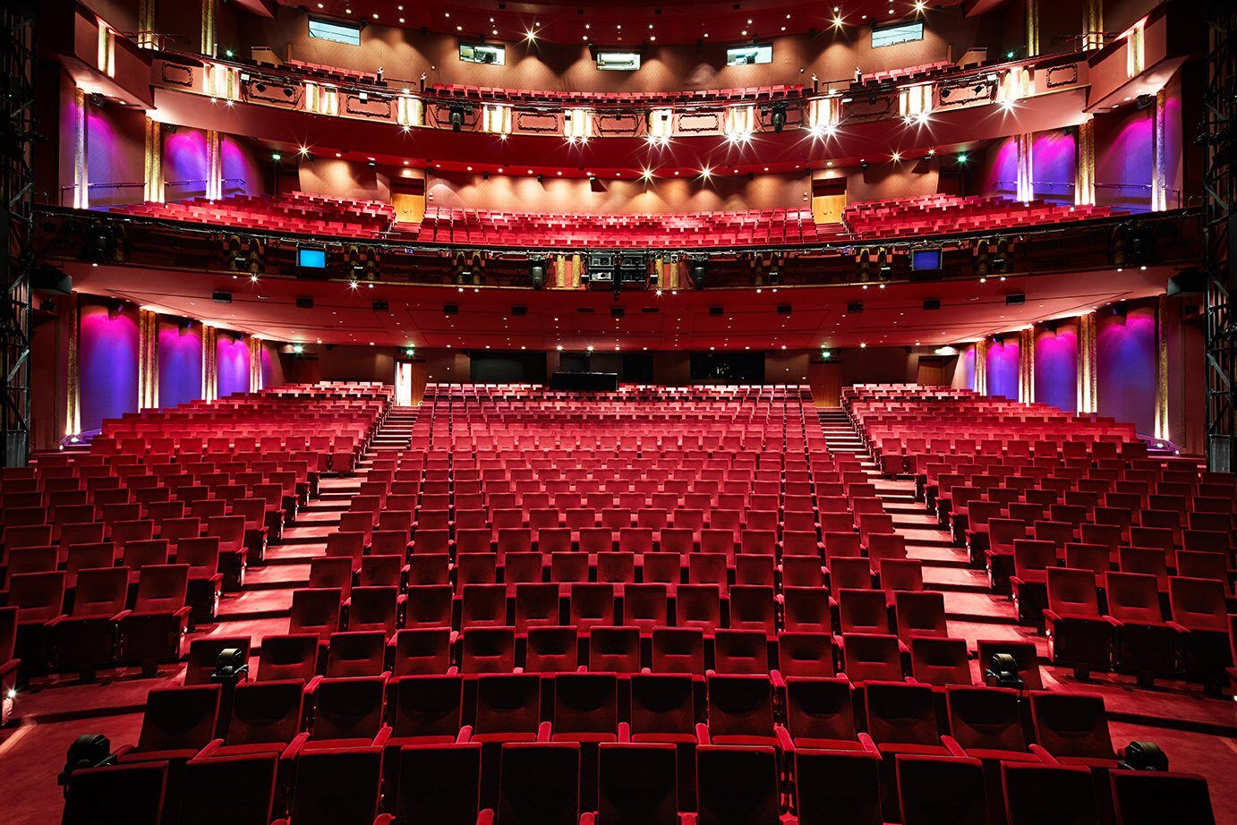 The interior view of a theater that is full of empty seats as viewed from the stage looking outwards.
