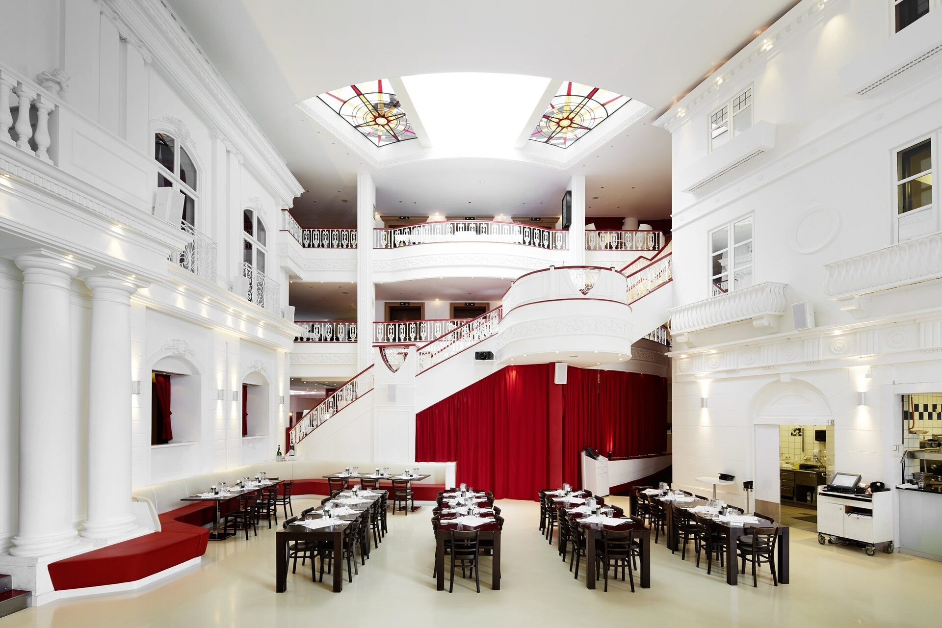 A large white room that is full of tables and chairs with a big staircase in the background.