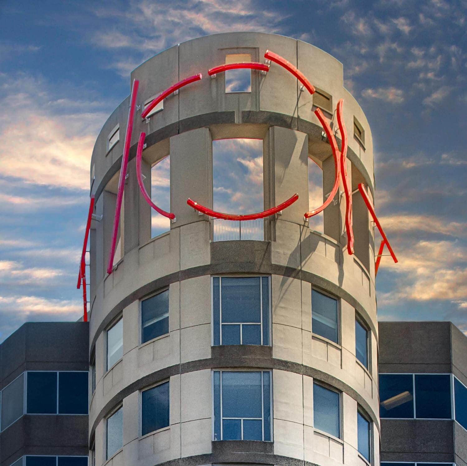 A tower with the sky reflected in its windows and red scupture on the exterior.