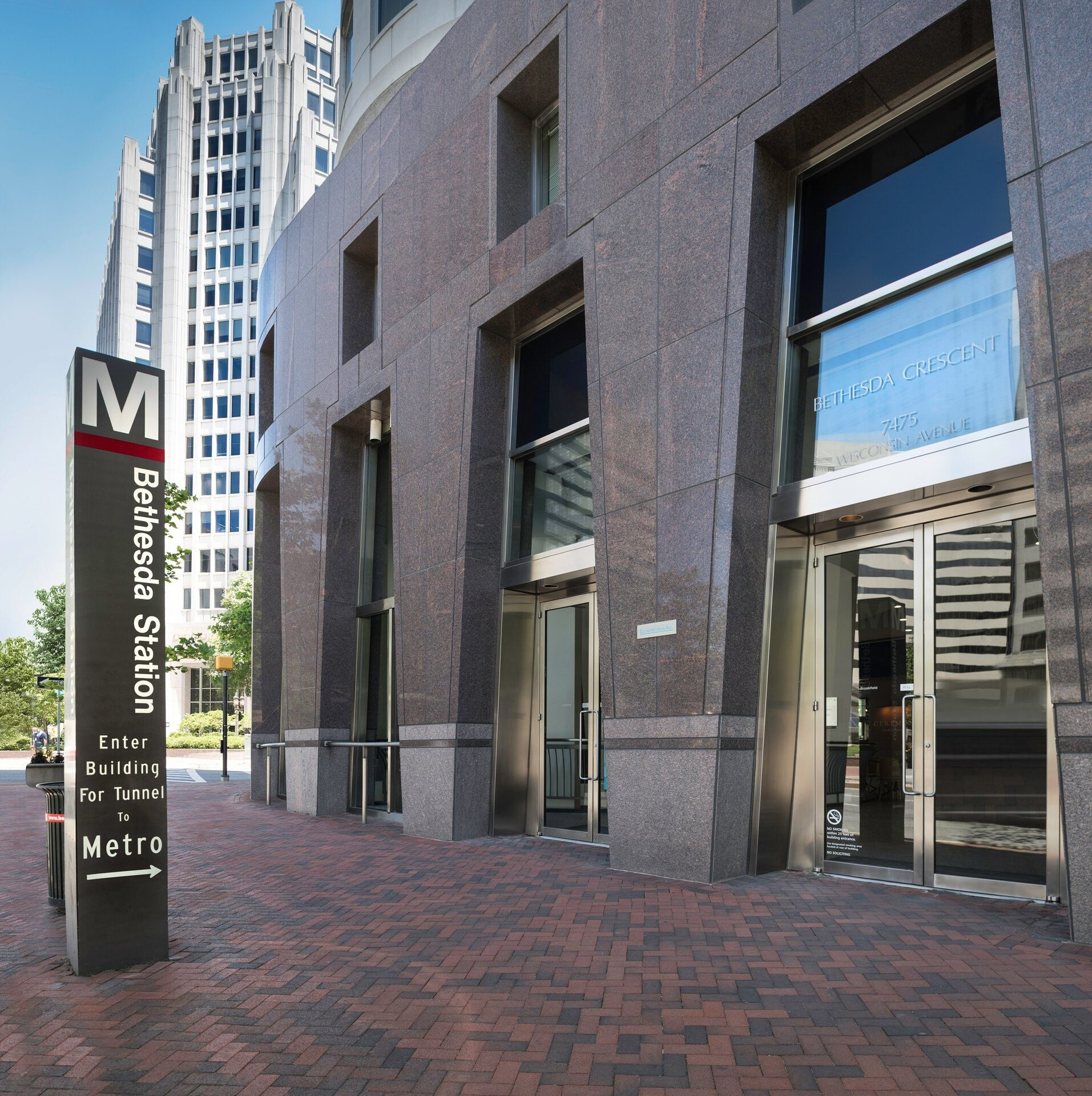 """Entrance to a building with a sign that says """"M Bethesda Station Enter Building for Tunnel to Metro"""". The sign has an arrow that points to the building."""