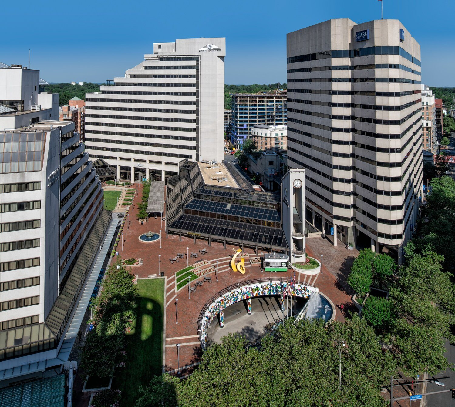 A walking area that is at the base of three different office buildings that are located in a downtown area in a city.