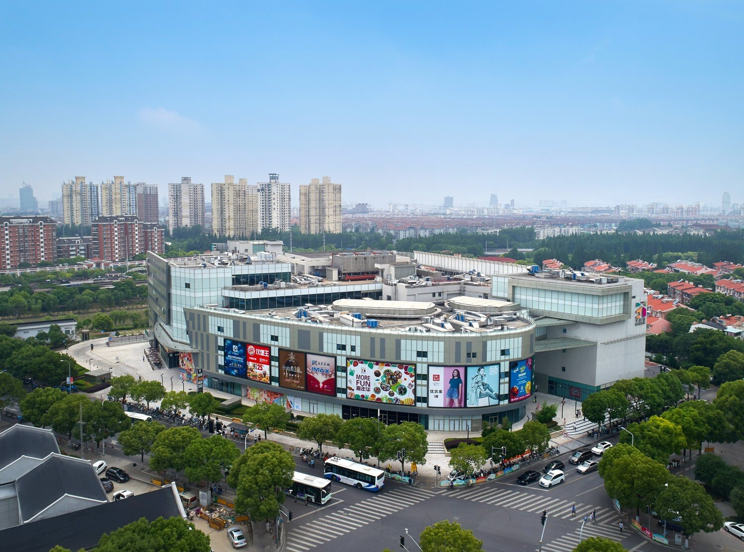 A large shopping center that has ads around the outside of it and it is near a large city that has some tall buildings in it.