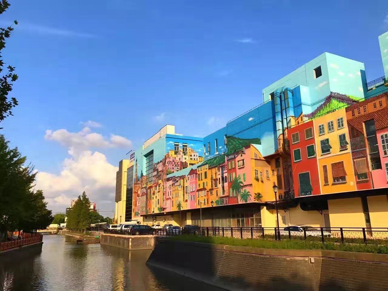 A building that is next to a river and the building is painted in a lot of colorful ways to make it look older.