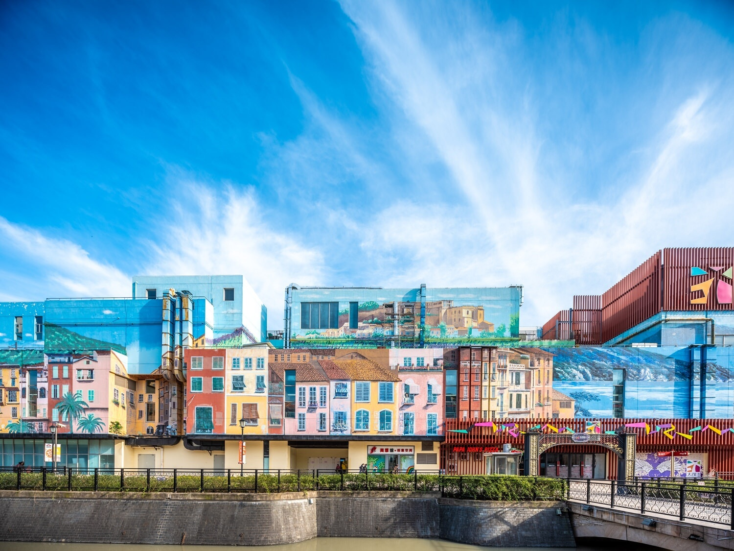 Some buildings that are painted to be more colorful and whimsical than they would be normally along a river.