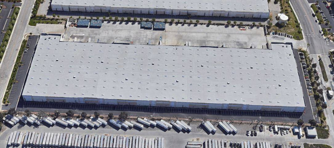 Top view of warehouse with trucks that are parked in the delivery area of the lot.