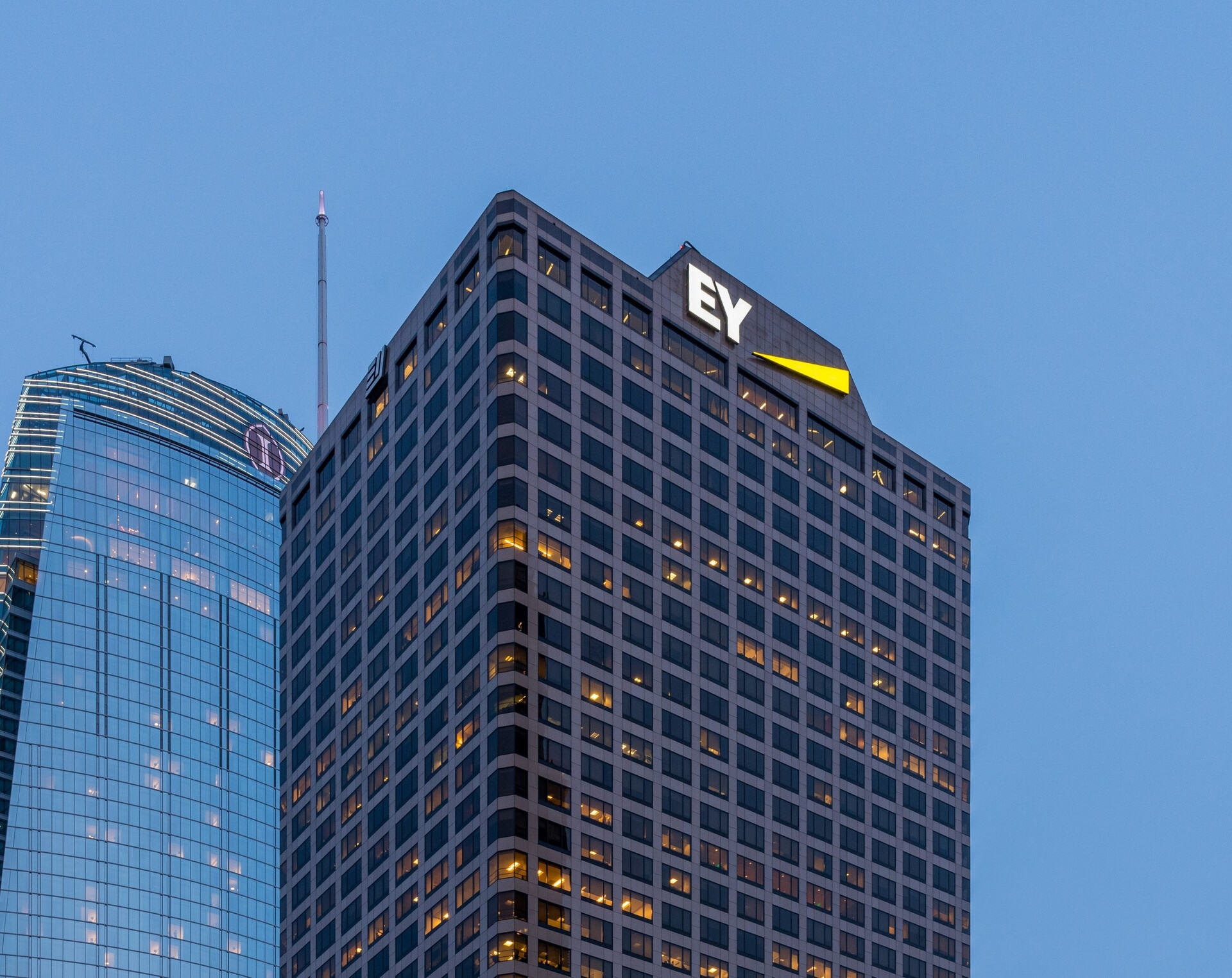 A tall building that is curved and has a lot of glass on it and there is an EY logo at the top of it