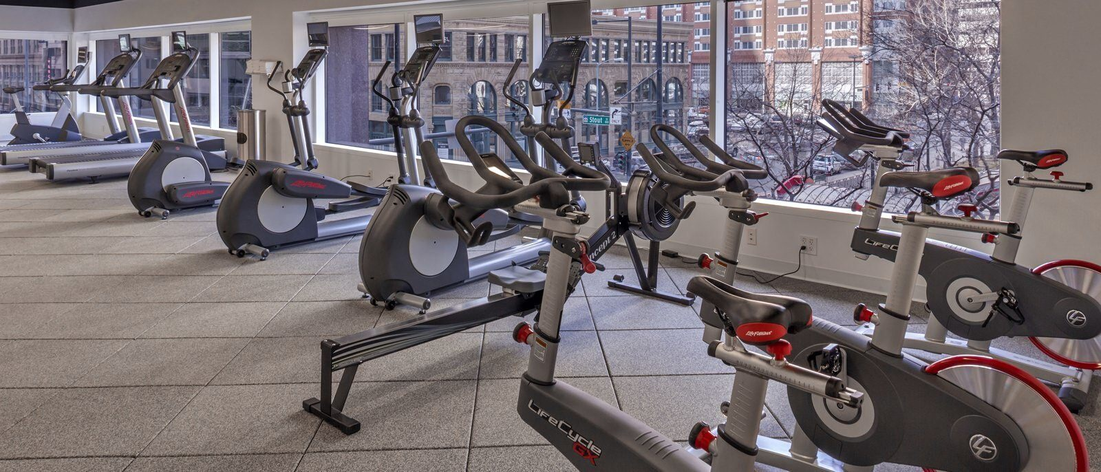 Inside of a gym with stationary bikes, ellipticals, and treadmills that look out onto a city street.