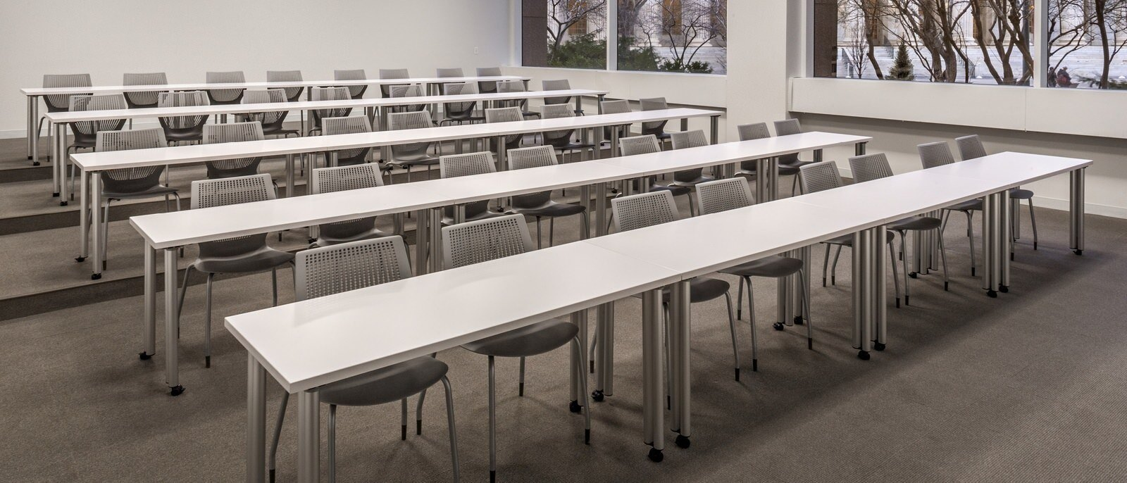 A classroom with five long white tables and multiple chairs.
