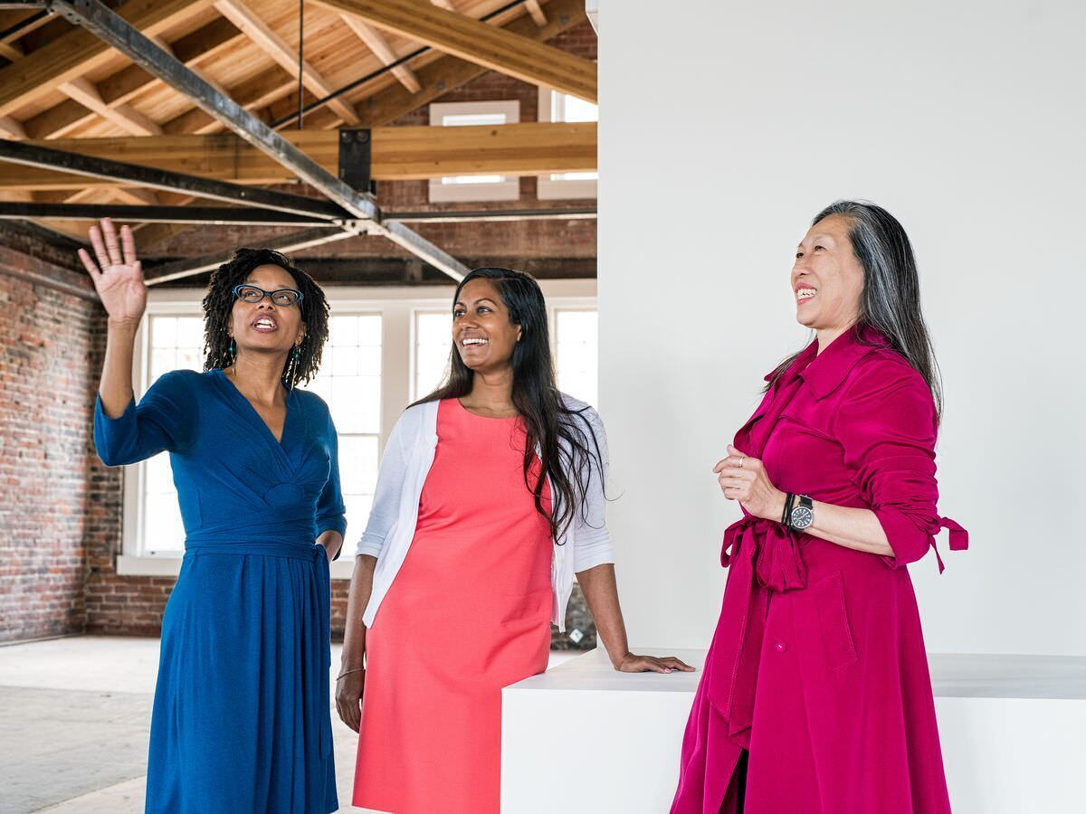 A group of women wearing dresses with different colors looking at the interior of a white room.