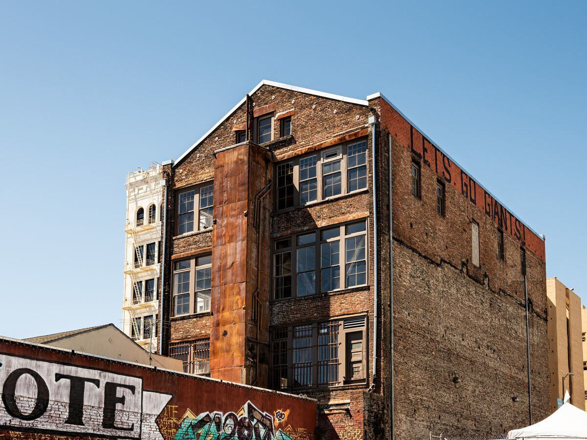 An old building made of bricks in the middle of a busy city underneath a blue sky.