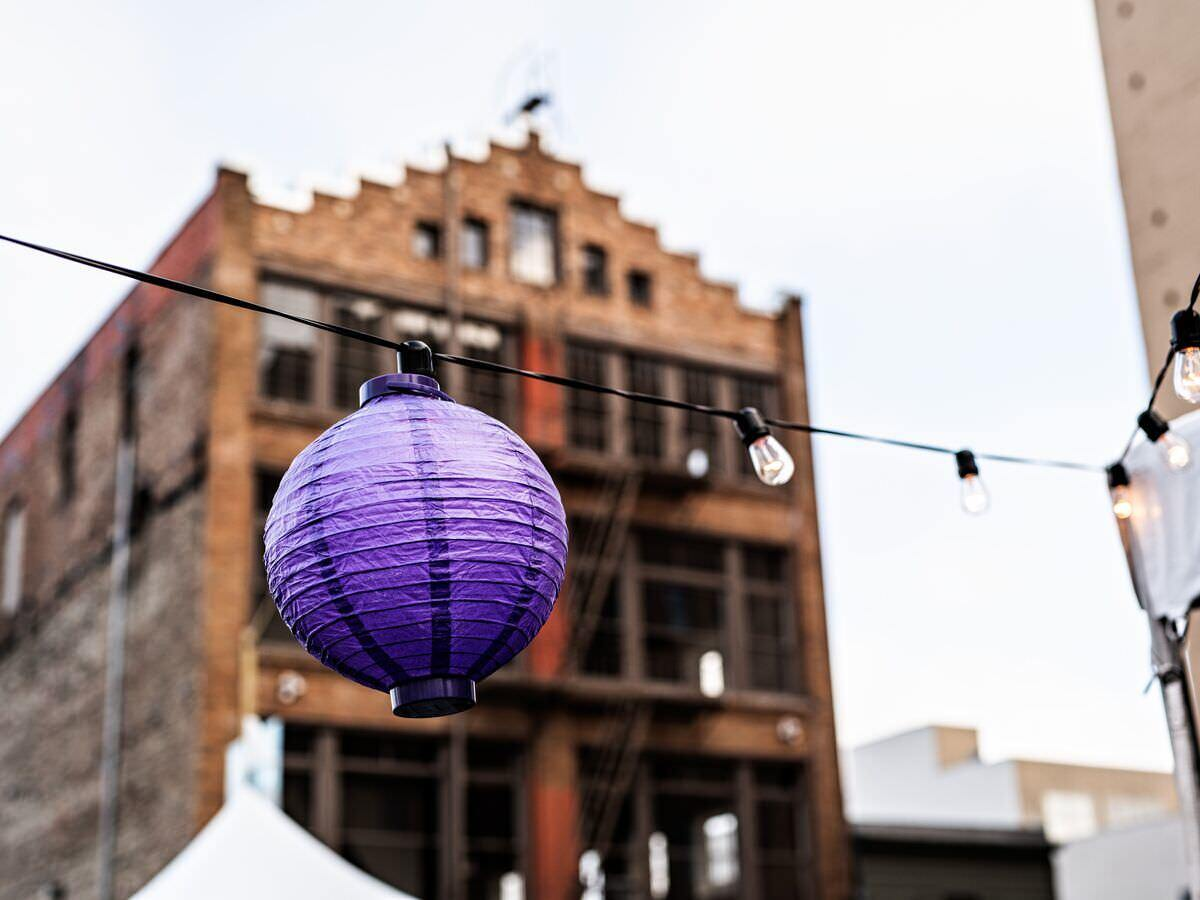 A purple paper lantern hangs on a wire of lights in front of a large brown building.
