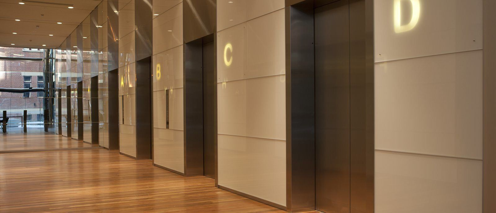 Elevators in a hallway with wooden floors labeled A, B, C, and D.