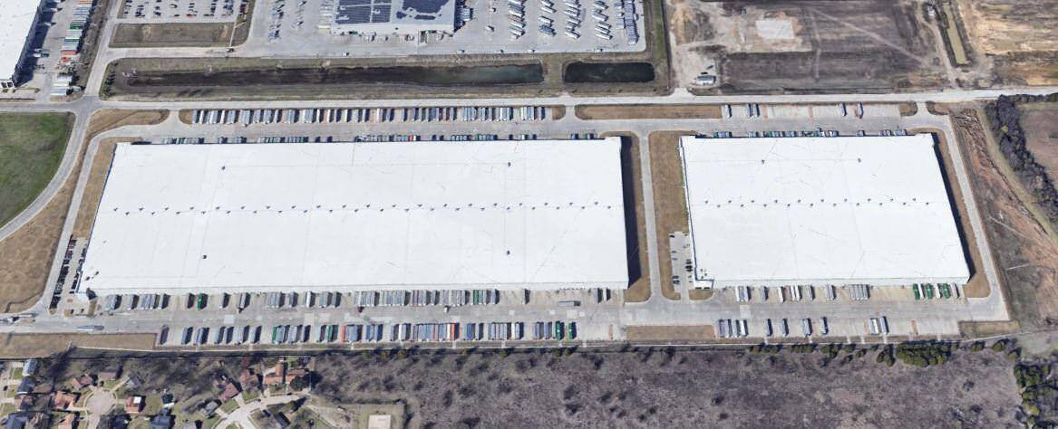Aerial view of two warehouses with parking for trucks.