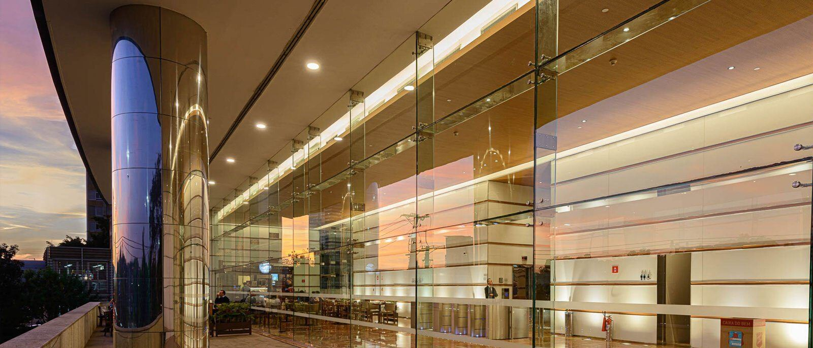 A building that has large glass windows and doors and stainless steel columns on the outside of it.