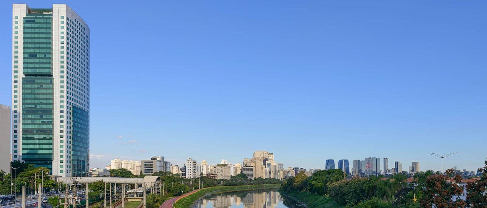 Outdoor city view of sky tall buildings and river seen with many trees and roads seen with cars