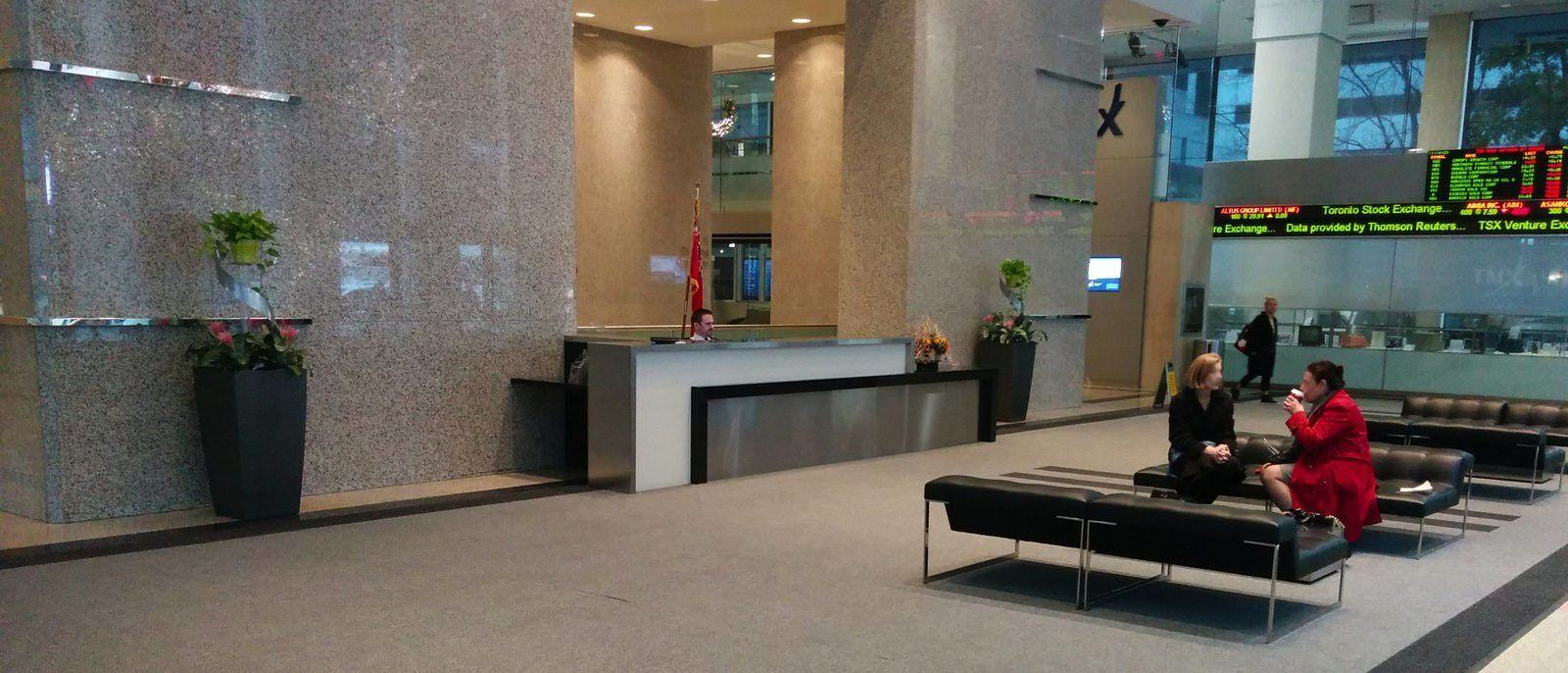 Two people sitting on couches that are located in the lobby of a large building that is likely a hotel.