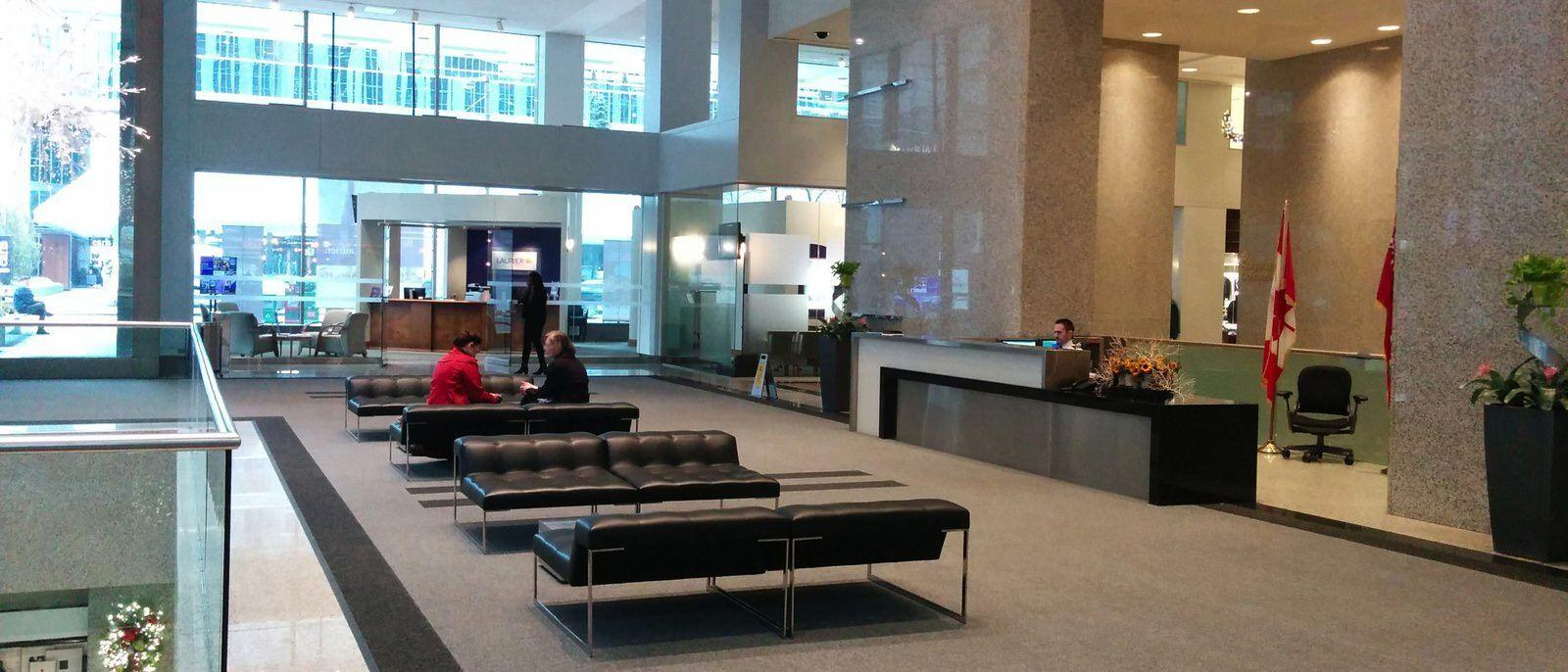 A few people sitting on furnitures that is within a large lobby inside of a big building.