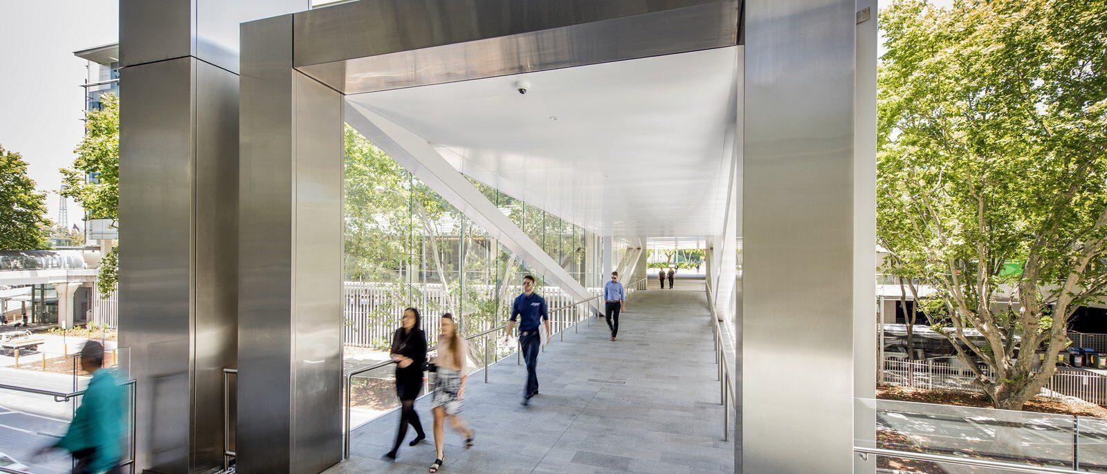 People walking in glass walkway between two buildings