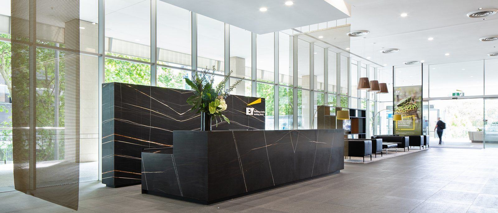 A lobby of a building that has a large black desk in the middle of it and a sitting area off to the side of it.