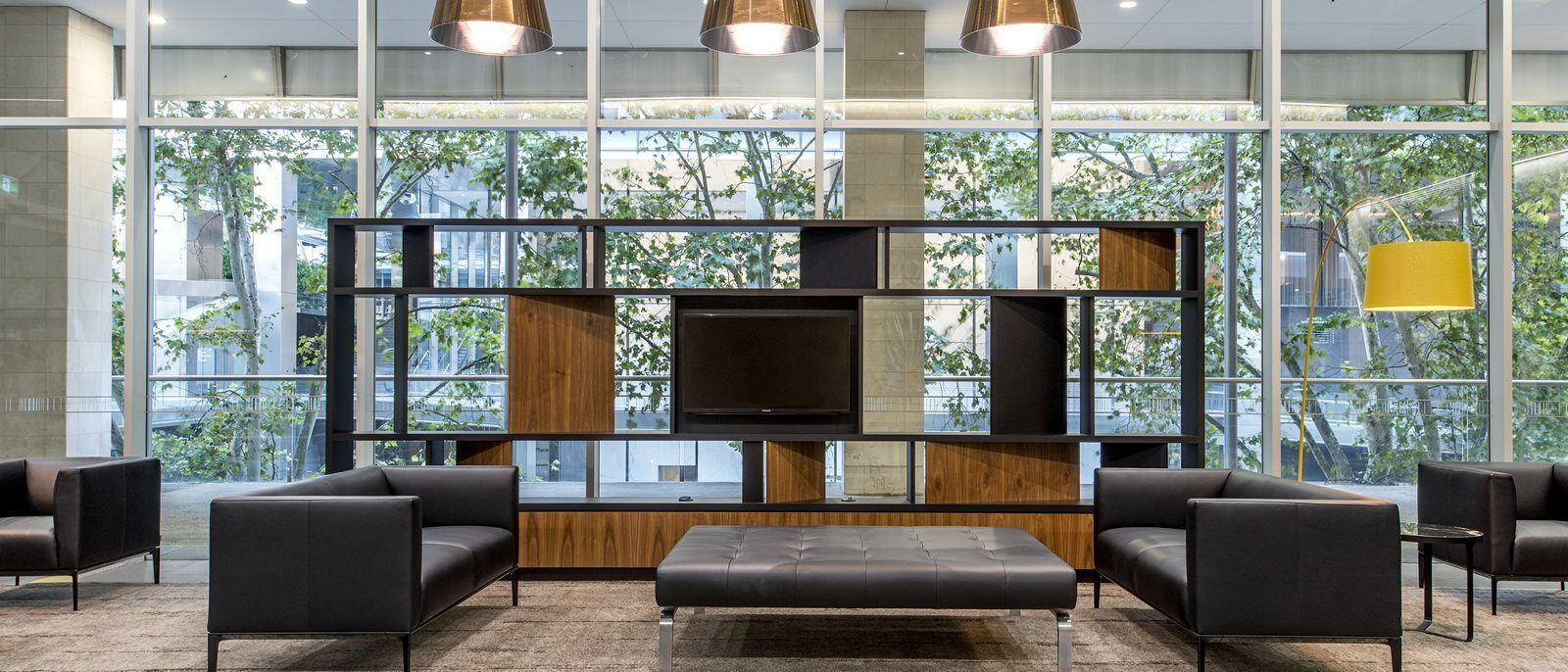 A sitting area in a lobby that has couches and a TV in a large piece of furniture.