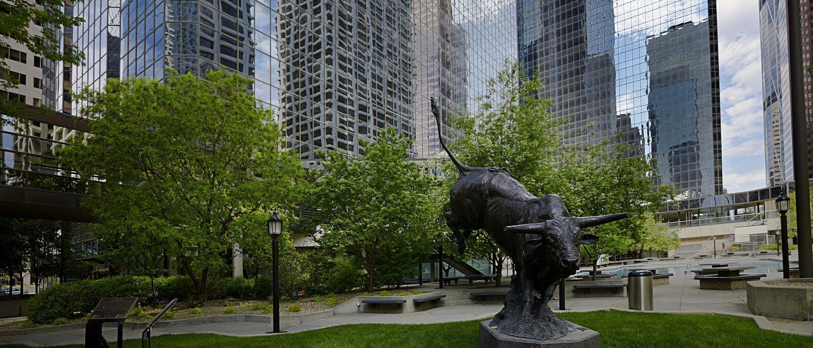 An green park within a city with a sculpture of a bull rearing its back lags.