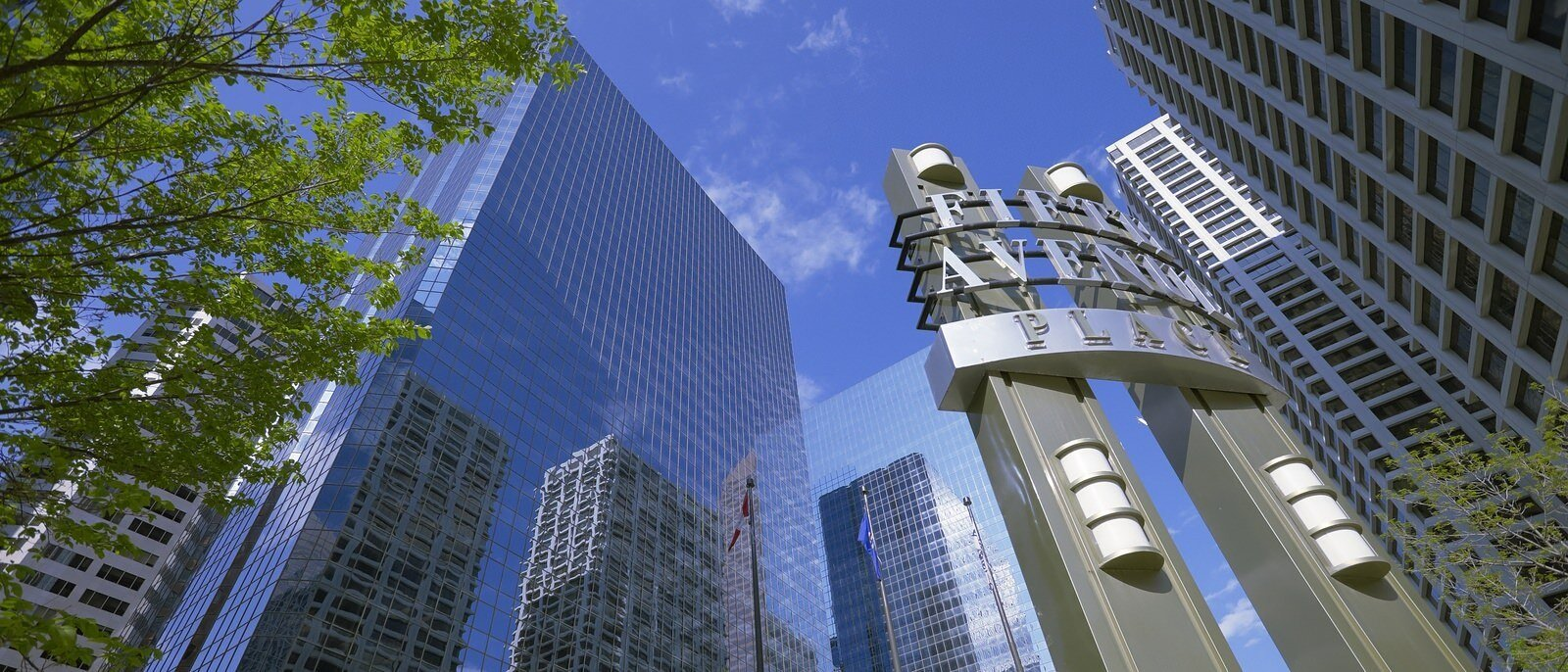 """View looking up a building with a sign in the foreground that says """"Fifth Avenue Place"""""""