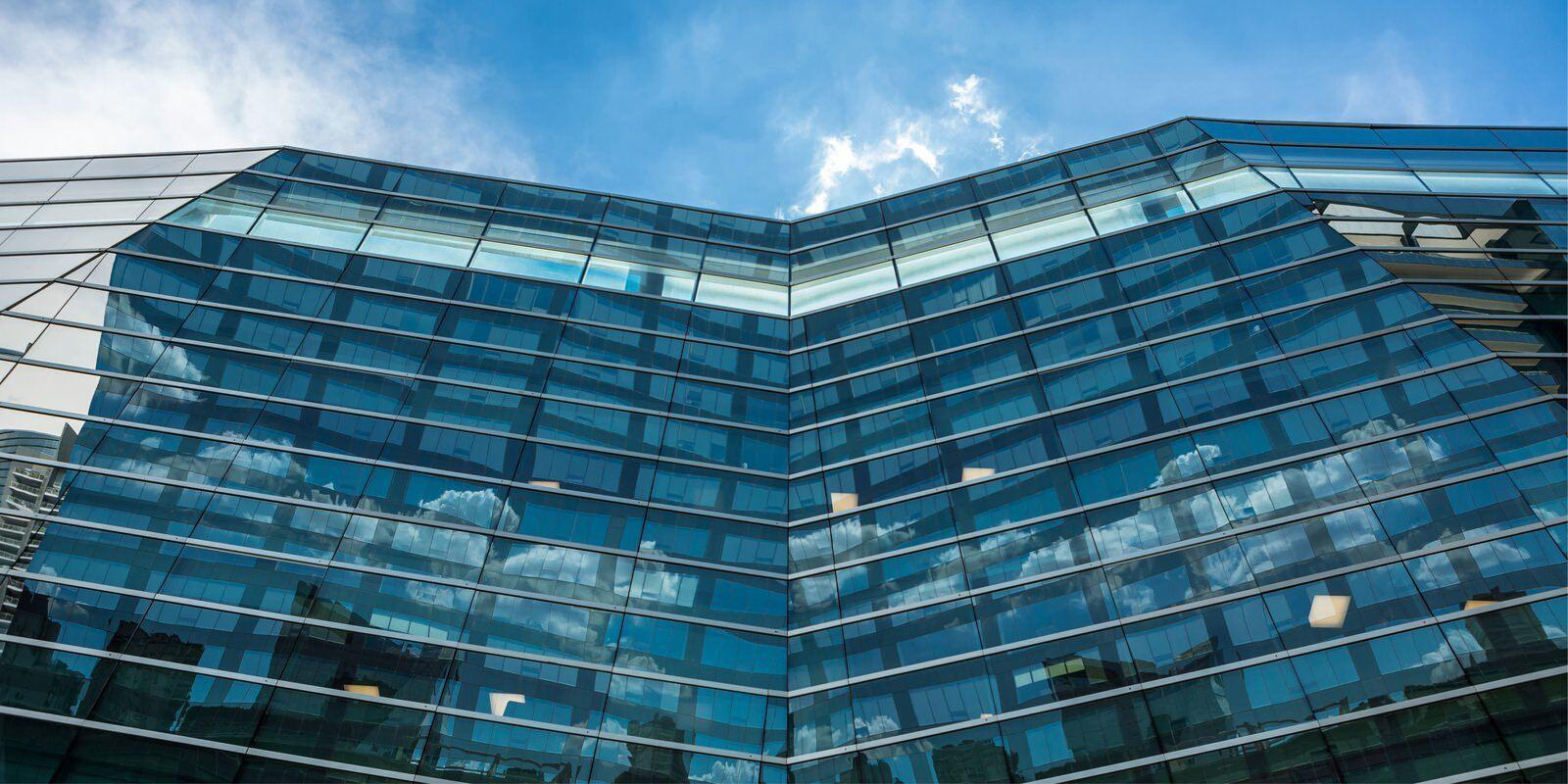 Upward view of a large building that is covered with glass windows with a blue sky above.