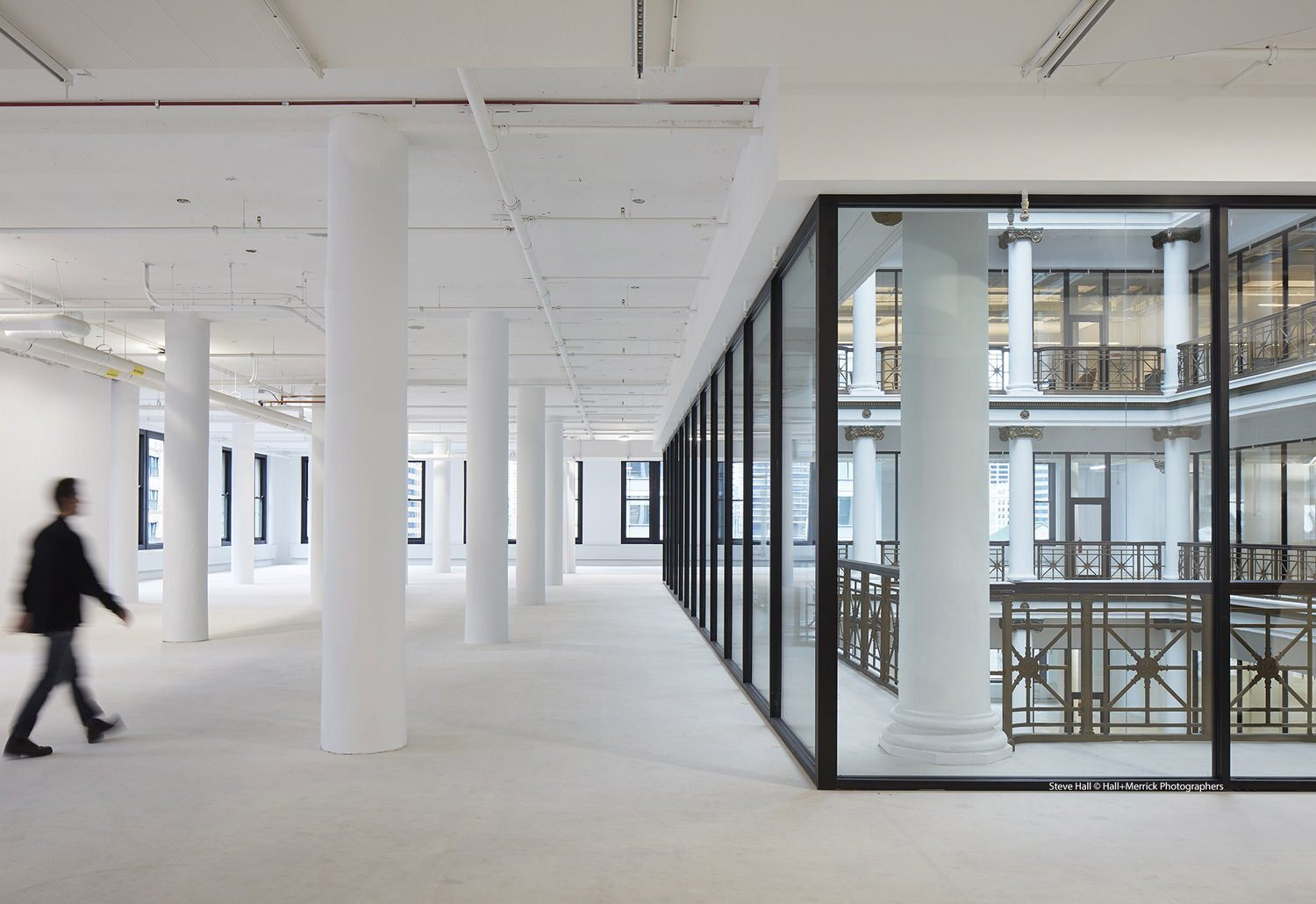 A person in a suit is walking in an empty white building with a glass interior and white columns.