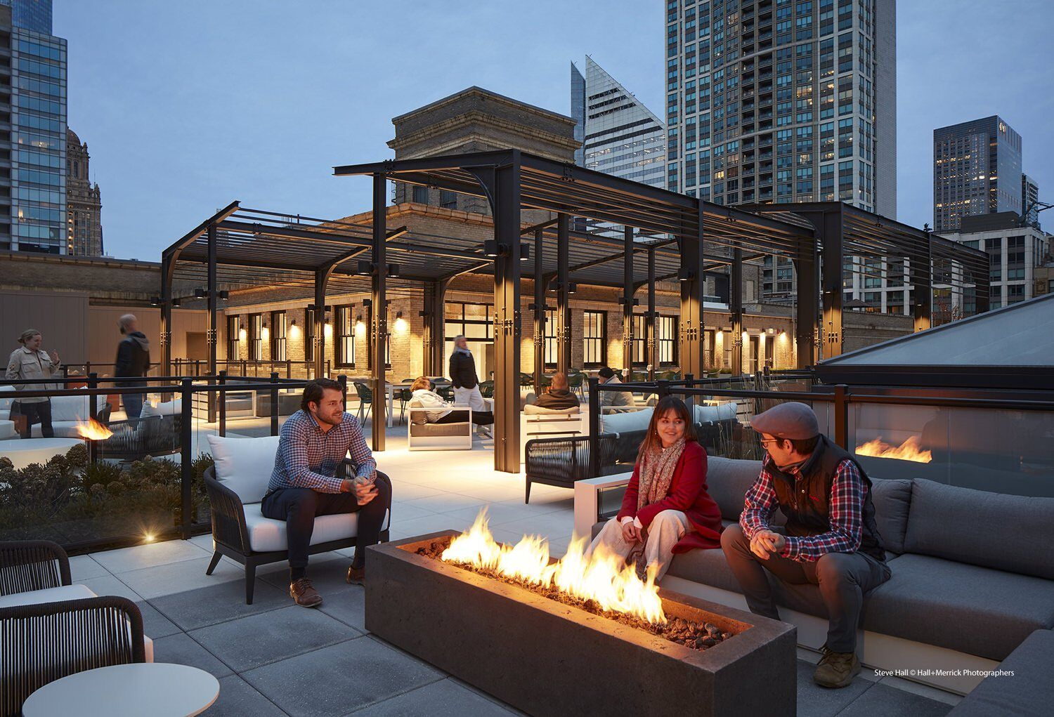 A group of people are sitting around a fire pit outdoors on the top of a roof in a city area.