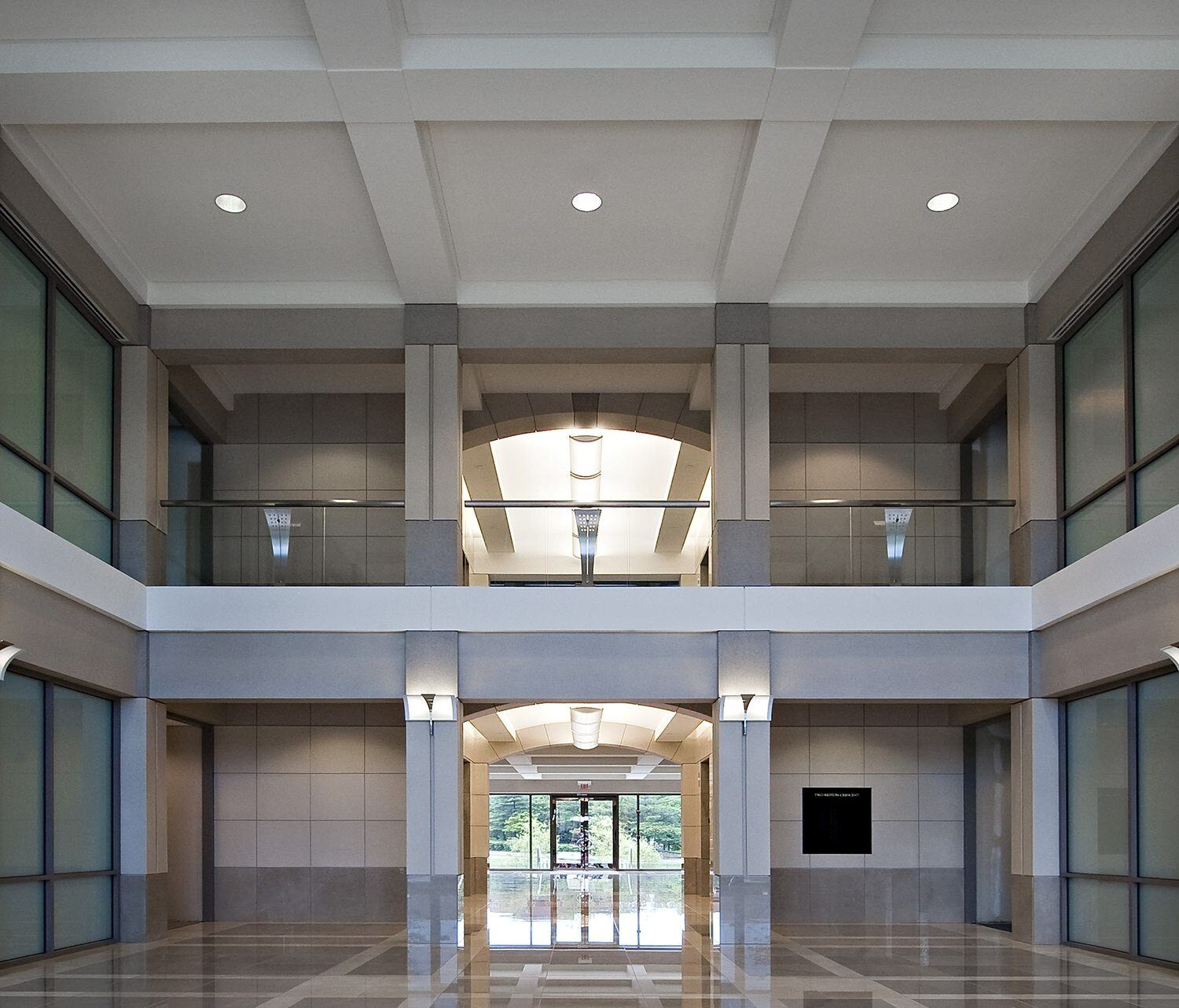 A view entering a building that has polished tile floors in it and a second floor looking over the entryway.