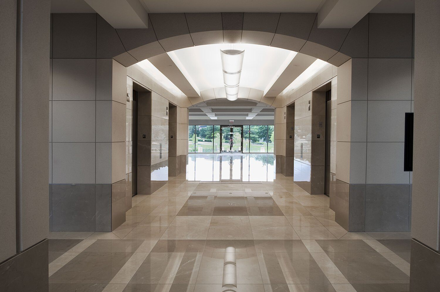A corridor that leads through an office building and it has four elevator doors off of it.