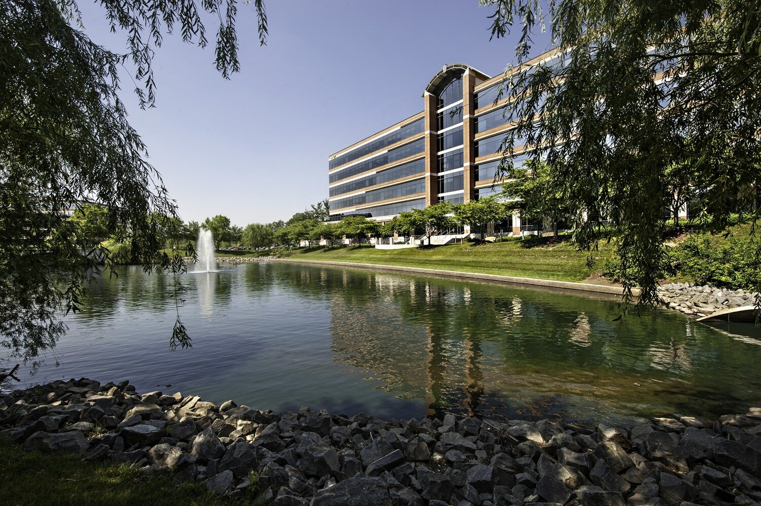 A big office building that is located next to a small lake that has a fountain in the middle of it.