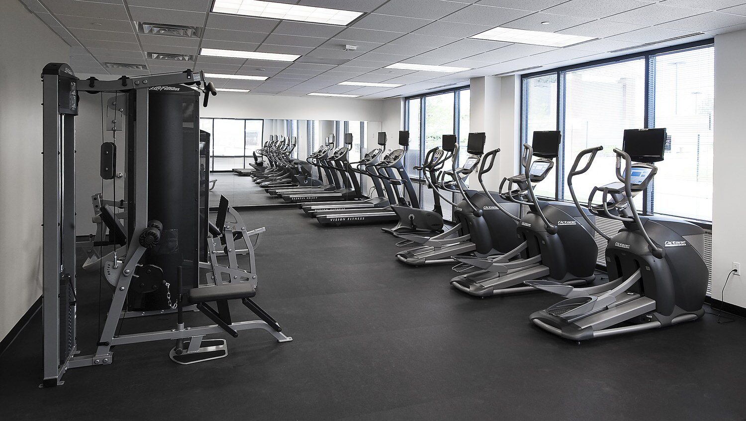 A lot of treadmills and elliptical machines that are located in a gym with rubber floors on it.