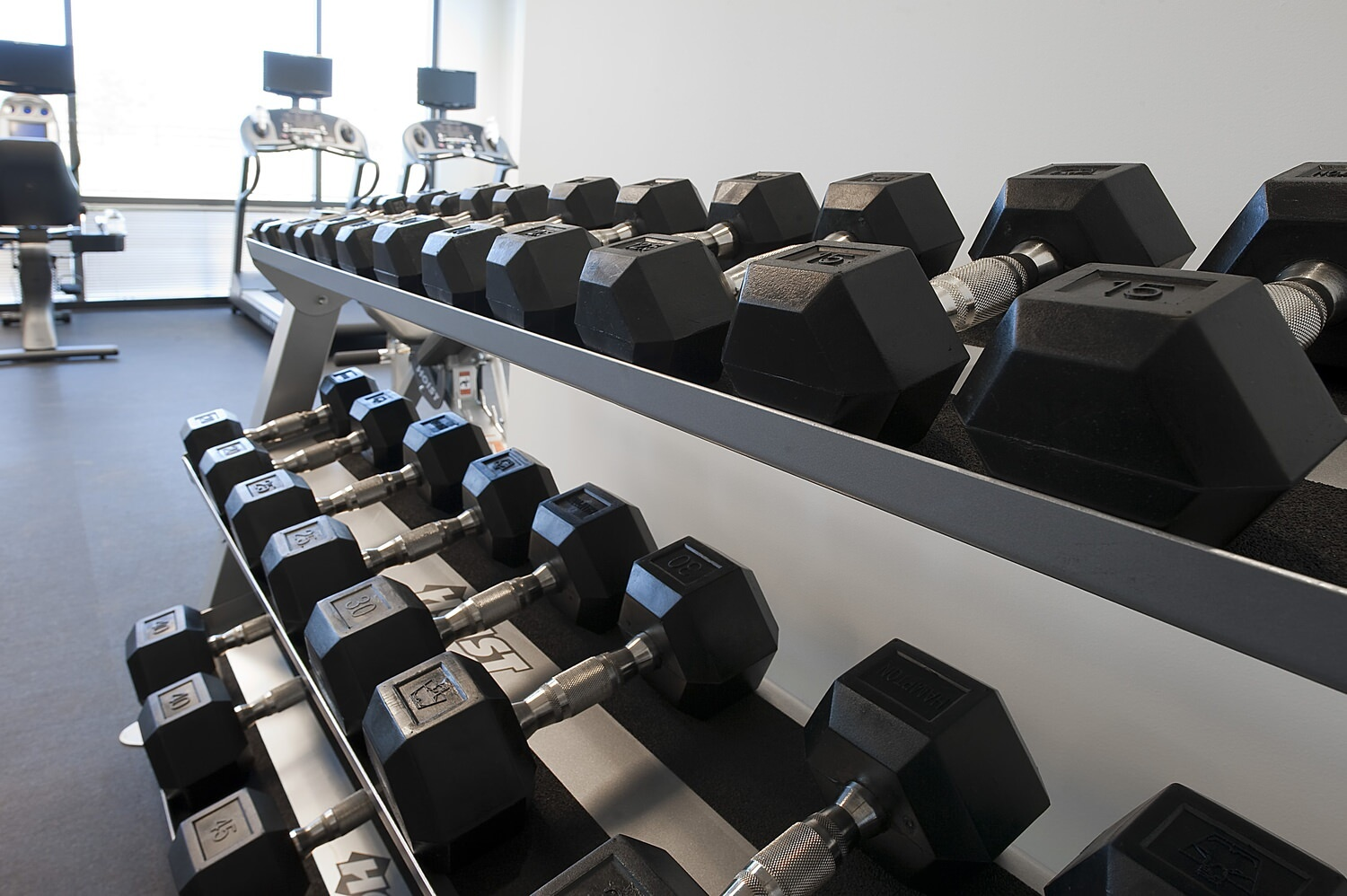 A gym that has barbells in a barbell rack and some treadmills and exercise machines behind them.