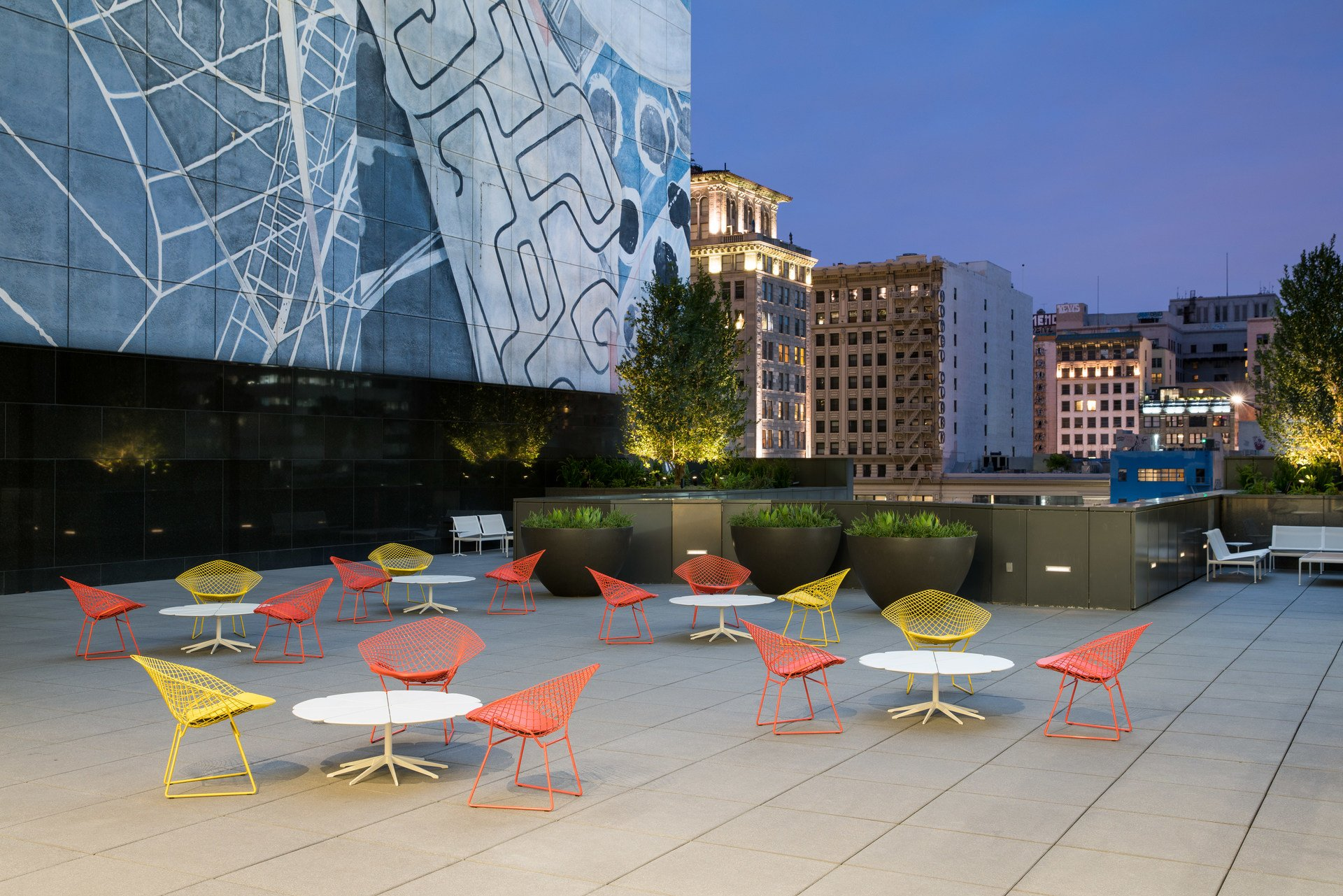 Outdoor seating area with red and yellow chairs at night. There is a mural on a building in the background.
