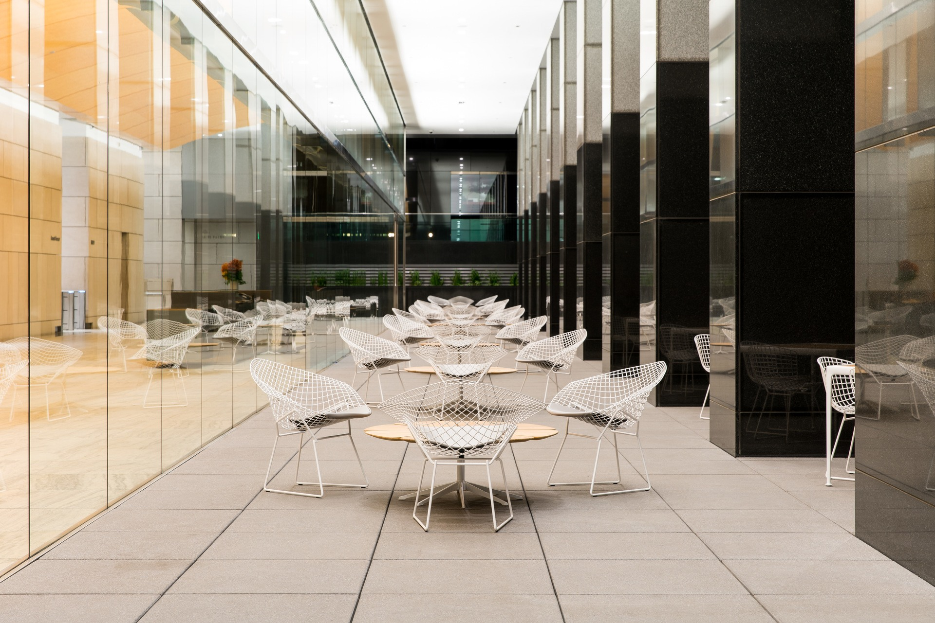 Outdoor seating area with white chairs and tables at night. The building entrance is to the left and has large, glass walls.