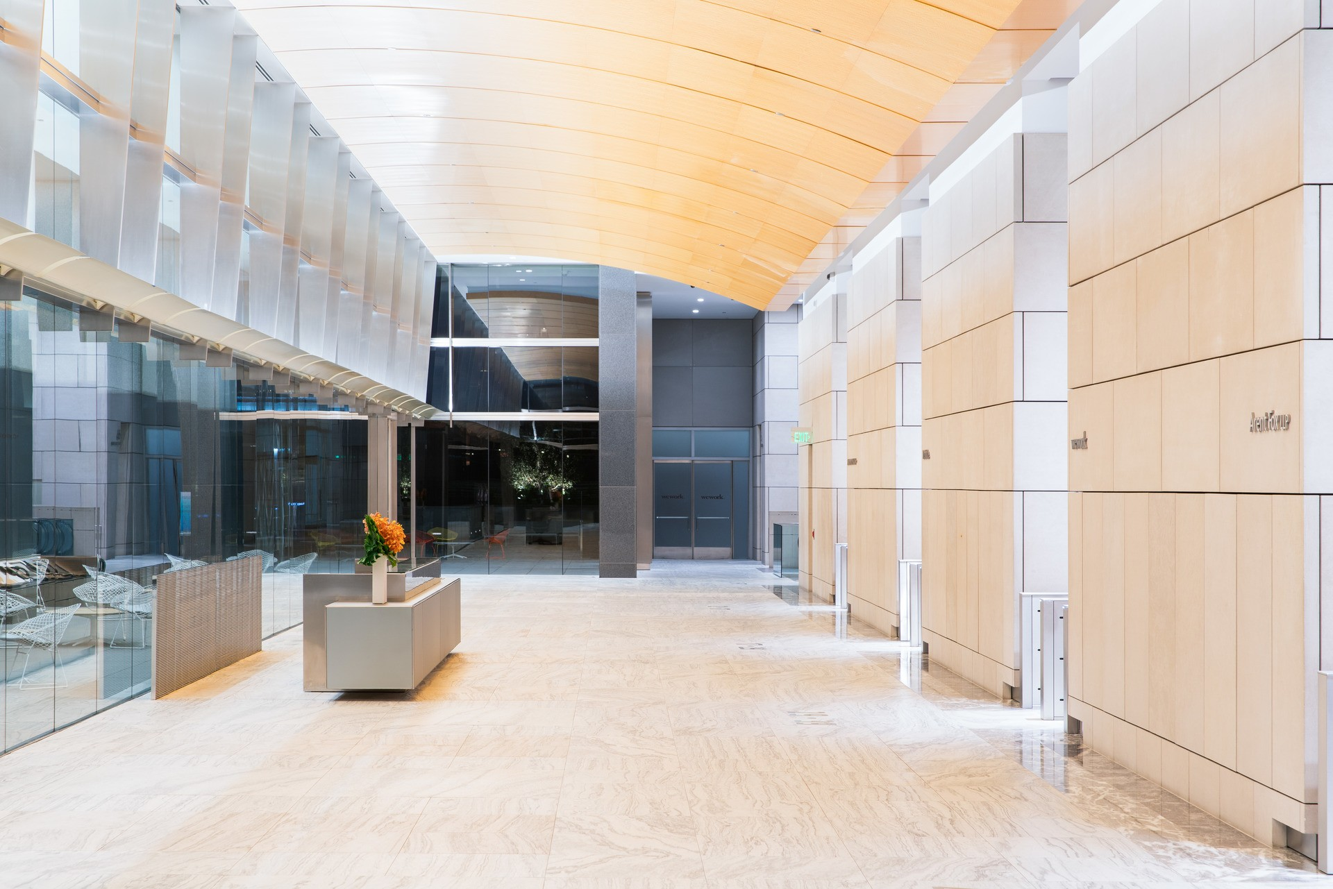 Lobby of a building with natural wood floors. There is a receptionist desk that has orange flowers on it.