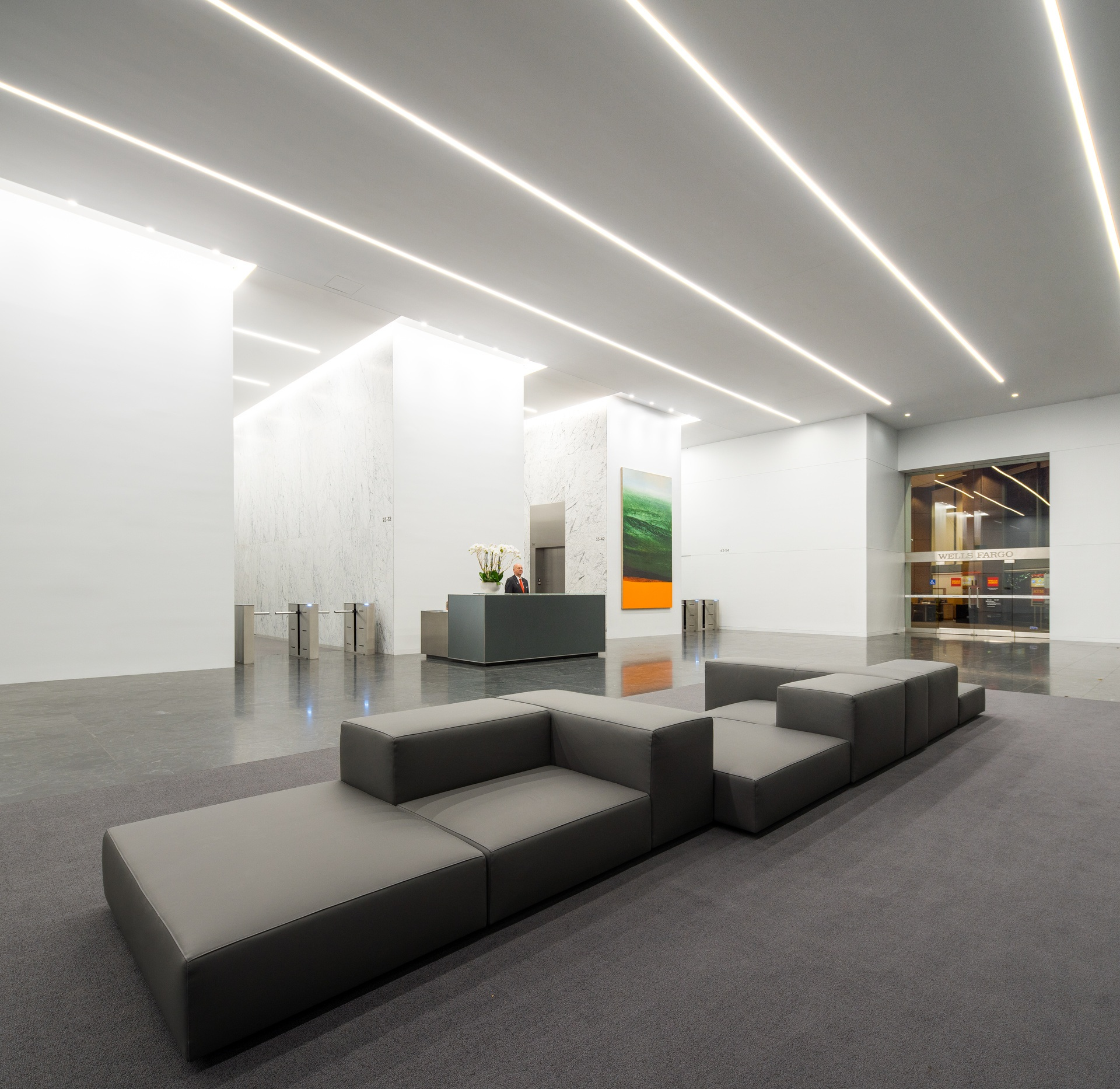 Bright lobby at night with gray couches and a turnstile.