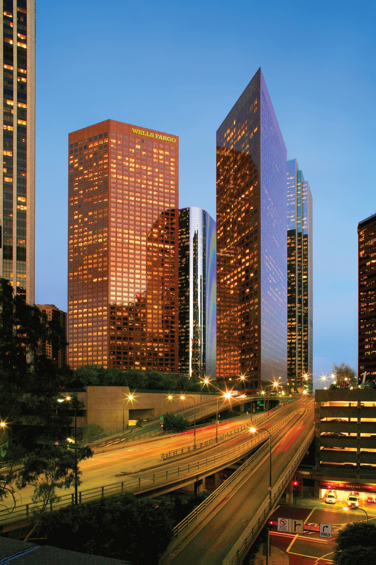 """A busy city street with two red skyscrapers in the background at twilight. One of the buildings says """"WELLS FARGO"""""""
